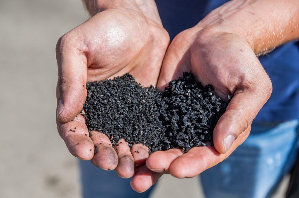 hands holding rubber crumb and rubber mulch