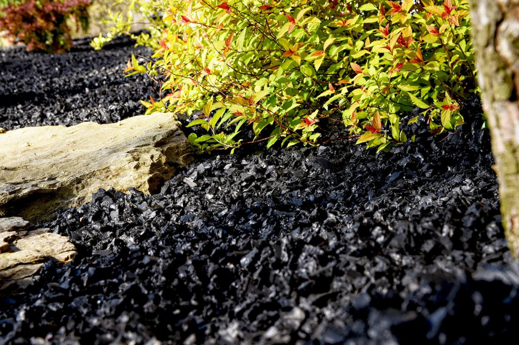 black rubber mulch with stone and plant